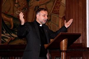 Le révérend Nadim Nassar priant pour la libération des sept responsables bahá'ís iraniens emprisonnés, à l'abbaye de Westminster, à Londres, le 27 mai 2014. Le révérend Nassar est le directeur et le co-fondateur de Awareness Foundation (Fondation de conscience), qui a pour but d'encourager les chrétiens à être des forces d'amour et de paix pour contrer l'intolérance et l'agression.