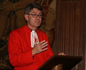 Le révérend Andrew Tremlett, chanoine de Westminster et recteur de St. Margaret's, accueillant les participants à la réunion commémorative à l'abbaye de Westminster, le 27 mai 2014 ; réunion qui a marqué le sixième anniversaire de l'emprisonnement de sept anciens responsables bahá'ís d'Iran.