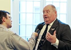 Le ministre des Collectivités locales du Royaume-Uni, le député Eric Pickels, répondant aux questions d'un reporter radio sur « Une année de service », une initiative patronnée par le gouvernement pour encourager le service bénévole au sein des neuf principales communautés religieuses du Royaume-Uni. Le lancement et le premier jour de volontariat du programme ont eu lieu au Centre national bahá'í de Londres, le 28 février 2012.