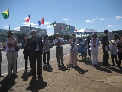 Le député brésilien Luiz Couto s'adresse aux militants des droits de l'homme à Brasilia ; ceux-ci portent des masques représentant les sept responsables bahá'ís iraniens emprisonnés.