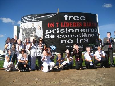 Au Brésil, les militants des droits de l'homme portent des masques représentant les sept responsables bahá'ís iraniens emprisonnés devant le Congrès national brésilien à Brasilia.