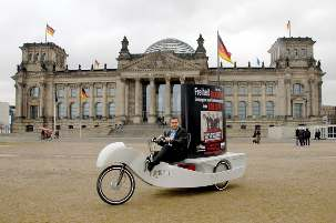 Au bâtiment historique du Reichstag à Berlin, le Membre du Parlement Serkan Tören a circulé sur un vélo spécial exposant l'image des sept responsables baha'is emprisonnés en Iran.