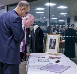 Le député Eric Pickles, secrétaire d'État aux Communautés et au Gouvernement local – sur la droite – examinant des objets personnels et historiques associés à 'Abdu'l-Bahá, au cours d'une réception organisée par le gouvernement britannique pour la communauté bahá'íe, le 28 novembre 2012.