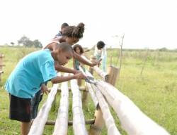 À Agua Azul, des jeunes participent à la construction de bancs entourant une zone où les plantes sont cultivées pour le terrain entourant le site de la maison d'adoration bahá'íe.