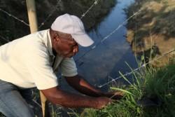 Don Hernan Zapata plante de nouveaux arbres le long d'une clôture entourant le site de la maison d'adoration.