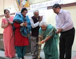 Allumage d'une lampe. De gauche à droite : Mme Lalita Sharma (la maîtresse de cérémonie sur le podium), Mme Shirin Mahalati, M. Ranjana Sehgal, M. Mishra, M. Janak Palta McGilligan et M. Singh.