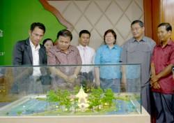 L'architecte explique sa conception au président du conseil provincial sous le regard du gouverneur Sophal