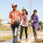 Des jeunes volontaires portant des plants de frangipanier