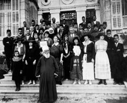 Un groupe de bahá'ís et d'autres personnes en compagnie de 'Abdu'l-Bahá à l'extérieur de sa maison à Haïfa. Deux soldats indiens se trouvent au dernier rang. (vers 1918).
