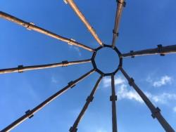 Les neuf mâts en bois qui formeront le dôme intérieur de la maison d'adoration sont couronnés par une structure en acier qui contiendra le plus grand nom, une fois le temple achevé.