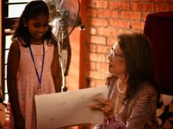 En Malaisie, la commémoration nationale de la communauté bahá'íe, marquant le bicentenaire de la naissance de Bahá'u'lláh, a accueilli des invités de tous les âges et de tous les horizons pour une exploration créative de la vie et des enseignements de Bahá'u'lláh. Dans la zone 11 de l'exposition, les enfants ont partagé avec les invités leur travail dans les classes bahá'íes. Ici, Dato 'Halimah Mohd Said – présidente de l'Association des voix de la paix, de la conscience et de la raison – examine une œuvre d'art avec l'une des fillette participante.