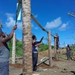 Des jeunes et des adultes travaillent ensemble à la construction d'une serre sur le territoire kalinago.