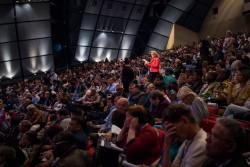 Des délégués écoutent attentivement, beaucoup bénéficiant des traductions simultanées, pendant qu'un représentant de la France fait une intervention.