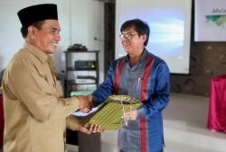 M. Haji Ibnu Hasan Muchtar, chercheur principal du ministère indonésien des Affaires religieuses, recevant un cadeau de la communauté bahá'íe d'Indonésie.
