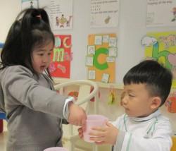 La notion de service est intégrée au programme de l'école des Nations. Ici, une élève de maternelle offre de l'eau à son camarade de classe lors d'une leçon.