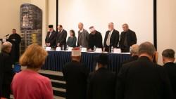 Le père Yousef  Yakoub (à gauche) récitant la prière de saint François d'Assise en arabe, anglais et hébreux dans le recueillement des membres de l'auditoire et des panélistes (à partir de la gauche) : l'émir Muhammad Sharif Odeh, Shervin Setareh, secrétaire générale adjointe de la Communauté internationale bahá'íe, le rabbin Naama Dafni-Kelen, l'évêque Michel Dubost, le cheik Jaber Mansour, le rabbin David Metzger et le cheik Rashad Abo Alhigaa.