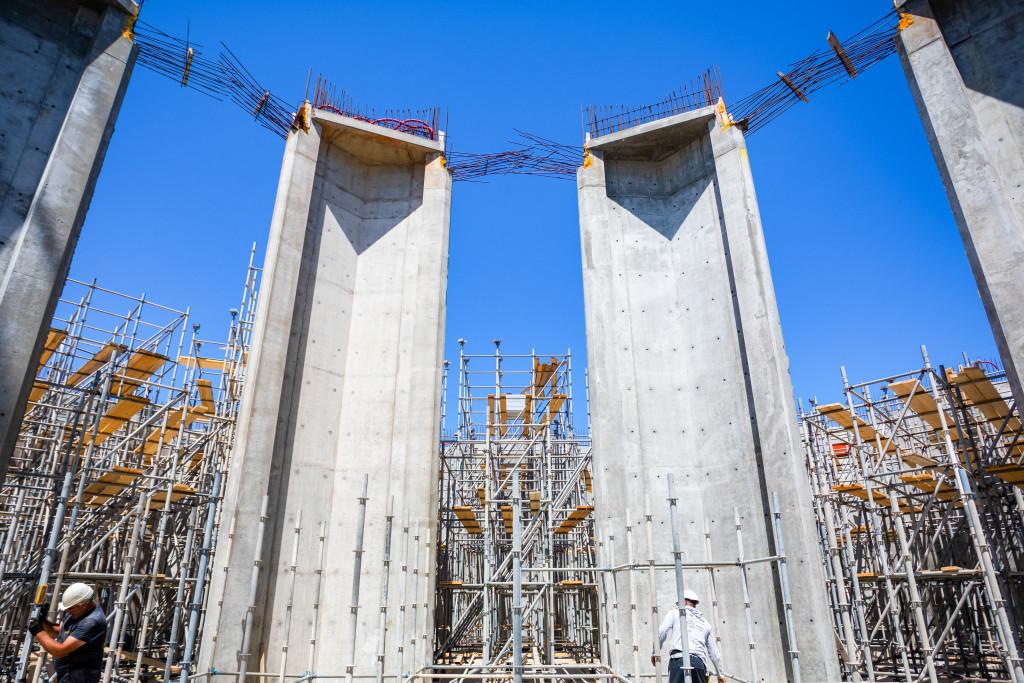 En plus des piliers, le premier ensemble de murs plissés est terminé et les préparatifs commencent pour le treillis que surplombera la place.