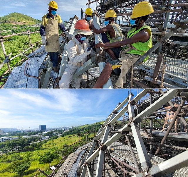 Des ouvriers positionnent les éléments en acier de la structure avec une grande précision tandis qu'un géomètre fournit des indications depuis le sol.