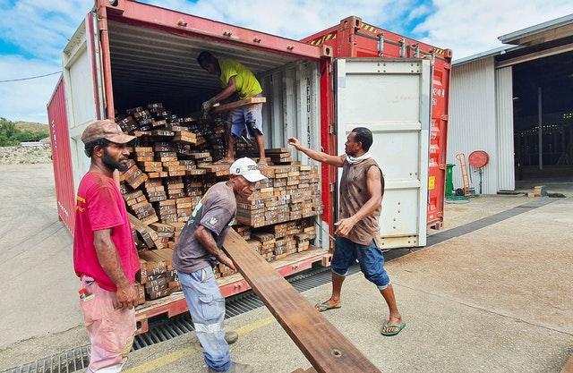 Des ouvriers déchargent une cargaison de bois recyclé qui recouvrira le dessous de chaque auvent d'entrée et se poursuivra à travers les murs intérieurs de l'édifice central.