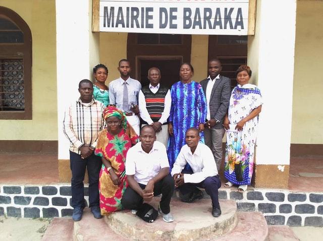 Rassemblement de personnes organisé conformément aux mesures de sécurité exigées par le gouvernement. Des membres de l'Assemblée spirituelle locale bahá'íe rendent visite à la maire adjointe de Baraka, Emerite Tabisha (debout, troisième en partant de la droite).