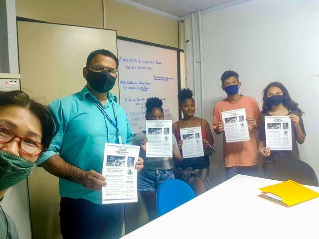 Des jeunes et l'animateur de leur groupe (à gauche) visitent le bureau d'un fonctionnaire municipal (deuxième à partir de la gauche) pour décrire les objectifs des programmes éducatifs offerts par les bahá'ís de Vila do Boa et pour partager leur vision de l'amélioration de l'environnement de leur quartier.